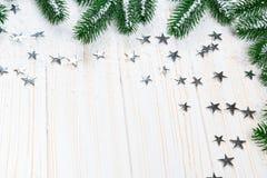 Albero di abete di Natale in neve con le stelle d'argento su fondo di legno bianco Immagine Stock Libera da Diritti