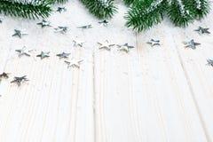 Albero di abete di Natale in neve con le stelle d'argento su fondo di legno bianco Immagini Stock Libere da Diritti