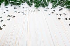 Albero di abete di Natale in neve con le stelle d'argento su fondo di legno bianco Fotografia Stock