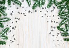Albero di abete di Natale in neve con le stelle d'argento su fondo di legno bianco Fotografie Stock