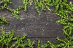 Albero di abete di Natale su un bordo di legno scuro con neve Natale o struttura del nuovo anno per il vostro progetto con lo spa immagine stock