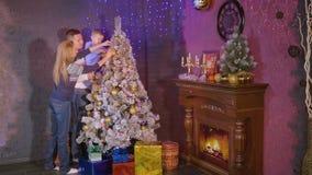 Albero di decorazione giovani madre della famiglia, padre e Natale e nuovo anno allegri felici del figlio insieme stock footage