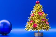 Albero di Natale artificiale giallo decorato con rosso a brillante Fotografie Stock Libere da Diritti