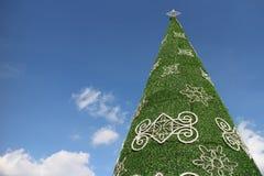 Albero di Natale artificiale gigante decorato con gli ambiti di provenienza del cielo blu Fotografie Stock
