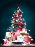 Albero di Natale brillantemente acceso con i presente Immagini Stock Libere da Diritti