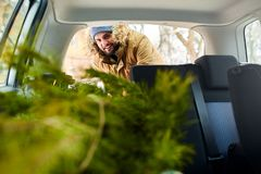 Albero di Natale di carico dell'uomo barbuto nel tronco della sua automobile, dentro la vista I pantaloni a vita bassa mettono l' fotografia stock libera da diritti