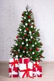 Albero di Natale con le palle variopinte ed i regali sopra il wa bianco del mattone Fotografia Stock