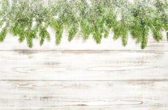 Albero di Natale con neve su fondo di legno immagini stock libere da diritti