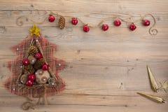 Albero di Natale d'annata con le palle della tela da imballaggio, i coni, i bastoni di legno e le mele rosse su fondo di legno be Immagini Stock Libere da Diritti