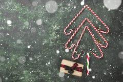 Albero di Natale dai bastoncini di zucchero e dalla scatola con il regalo su un BAC verde Immagine Stock Libera da Diritti
