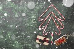 Albero di Natale dai bastoncini di zucchero e dalla scatola con il regalo su un BAC verde Fotografia Stock