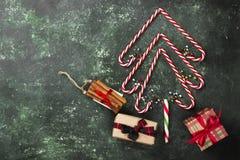 Albero di Natale dai bastoncini di zucchero e dalle scatole con i regali su un verde Immagine Stock