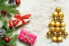 Albero di Natale dalle palle e dai rami di albero dorati dell'abete con i contenitori di regalo Immagine Stock
