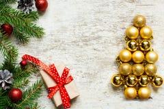 Albero di Natale dalle palle e dai rami di albero dorati dell'abete con il contenitore di regalo Fotografia Stock Libera da Diritti
