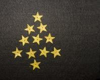 Albero di Natale dalle piccole stelle dorate su fondo nero Immagini Stock Libere da Diritti