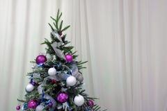 Albero di Natale decorato con le palle e le ghirlande su un fondo delle tende bianche Copi lo spazio Decorazione tradizionale per immagini stock libere da diritti