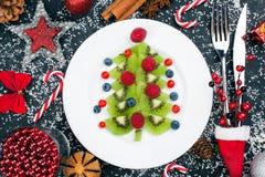 Albero di Natale del kiwi con il lampone, il mirtillo e l'uva di monte sulla tavola con la decorazione fotografia stock