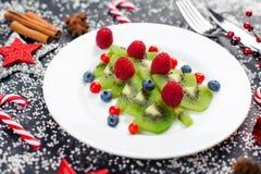 Albero di Natale del kiwi con il lampone, il mirtillo e l'uva di monte sulla tavola con la decorazione immagine stock libera da diritti