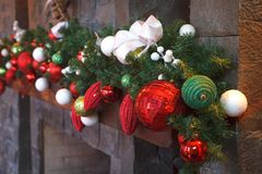 Albero di Natale/del nuovo anno con le decorazioni festive variopinte sul camino Immagine Stock