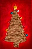 Albero di Natale della catena dorata su colore rosso Fotografia Stock