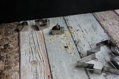 Albero di Natale della taglierina del biscotto di Natale e cuori e stelle gialle dello zucchero sulla tavola di legno fotografie stock