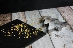 Albero di Natale della taglierina del biscotto di Natale e stelle gialle dello zucchero sulla tavola di legno immagini stock