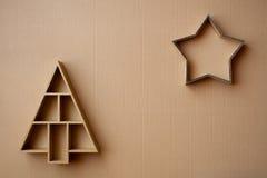 Albero di Natale e contenitori di regalo a forma di stella sul fondo del cartone Fotografia Stock Libera da Diritti