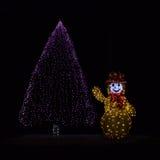 Albero di Natale e pupazzo di neve illuminati Fotografia Stock