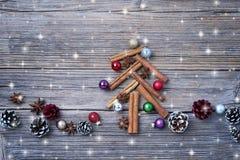 Albero di Natale fatto dai bastoni di cannella con la decorazione su fondo rustico Effetto della neve, spazio della copia Fotografie Stock Libere da Diritti