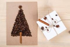Albero di Natale fatto dai chicchi di caffè e dal contenitore di regalo sul BAC di legno Immagini Stock