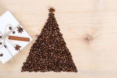 Albero di Natale fatto dai chicchi di caffè e dal contenitore di regalo sul BAC di legno Fotografia Stock