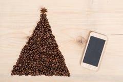 Albero di Natale fatto dai chicchi e dal telefono di caffè su backgr di legno Immagini Stock Libere da Diritti