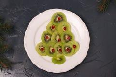 Albero di Natale fatto dal kiwi e dal melograno, idea creativa per i piatti festivi del nuovo anno e di Natale immagine stock