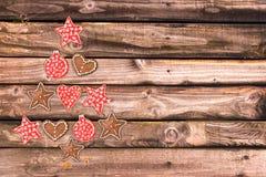 Albero di Natale fatto degli ornamenti rustici di legno sulle plance di legno Immagini Stock