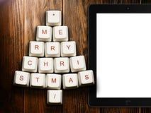 Albero di Natale fatto dei tasti del computer e del computer della compressa su fondo di legno Fotografie Stock