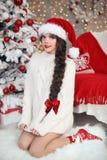 Albero di Natale Ragazza abbastanza teenager in cappello di Santa e bianco tricottato Fotografie Stock Libere da Diritti
