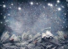 Albero di Natale sui giri dell'automobile del giocattolo sui rami dell'abete su fondo blu dar con neve dipinta Cartolina d'auguri immagini stock libere da diritti