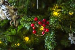Albero di Natale verde decorato con i giocattoli di Natale e una ghirlanda con le luci gialle Fotografie Stock