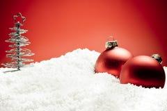 Albero di Natale vicino alle sfere rosse della decorazione su neve Fotografia Stock