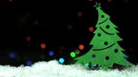 Albero di Toy Christmas in neve sopra la ghirlanda di lampeggiamento blured sui precedenti video d archivio