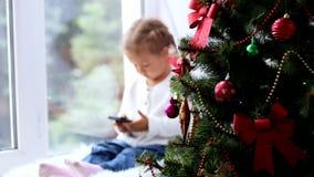 Albero e bambina decorati di Christmass con lo Smart Phone sui precedenti stock footage
