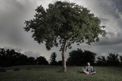 albero meditating del ragazzo sotto Fotografia Stock Libera da Diritti