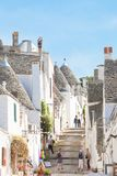 Alberobello, Apulia - JUNE 1, 2017 - Tourists walking through a. Alberobello, Apulia, Italy - JUNE 1, 2017 - Tourists walking through a traditional alleyway in stock images