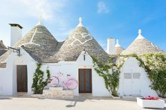 Alberobello, Apulia - A rose bicycle in front of a Trullo. Alberobello, Apulia, Italy - A rose bicycle in front of a Trullo royalty free stock photography