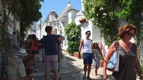 ALBEROBELLO ITALIEN - JULI 31, 2017: Scenisk sikt med turister i Alberobello, den berömda Trulli byn i Apulia lager videofilmer