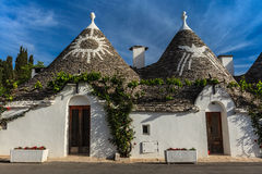 Alberobello, Italy. Trulli houses with painted symbols on the conical roofs in Alberobello, Italy, Puglia Stock Photography