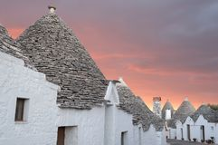 Puglia, Italy. Traditional conical roofed trulli houses on a street in Alberobello. Photographed early morning with red sky. Alberobello, Puglia, Italy stock image