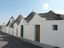 Alberobello's trulli on a line. A road of Trulli, the traditional house of the farmers of Alberobello, southern Italy stock photos