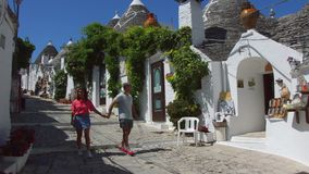 ALBEROBELLO WŁOCHY, LIPIEC, - 31, 2017: Sceniczny widok z kochającej pary turystyczny zaczarowanym pamiątkarskim sklepem w Albero zdjęcie wideo