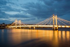 Albert Bridge and beautiful sunset over the Thames, London England UK. Albert Bridge, over the River Thames,Chelsea, London, England, UK, illuminated at night royalty free stock image